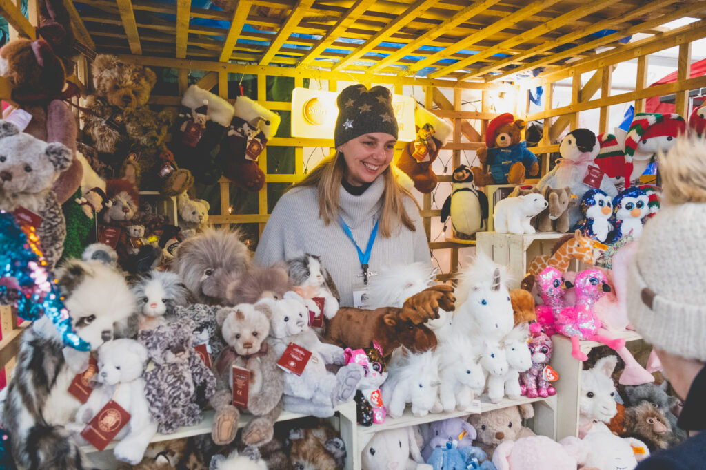 A happy exhibitor selling children's toys and gifts at Fowey Christmas Market