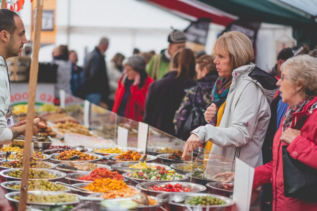 Visitors chosing a selection of charcuterie food at Fowey Christmas Market