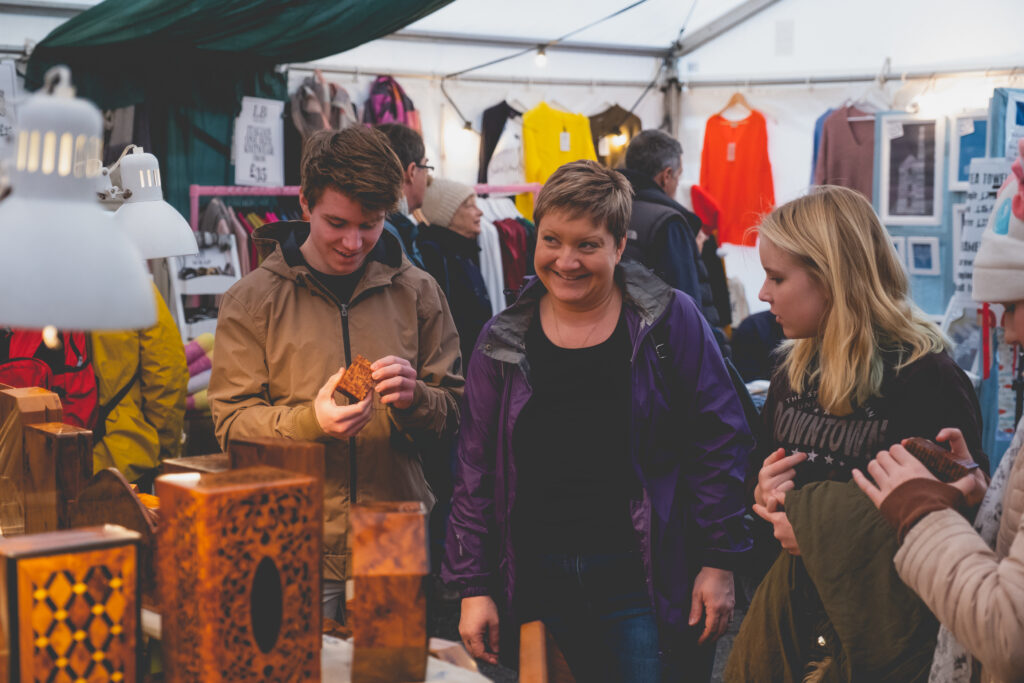 Happy visitors perusing hand crafted gifts at Fowey Christmas Market
