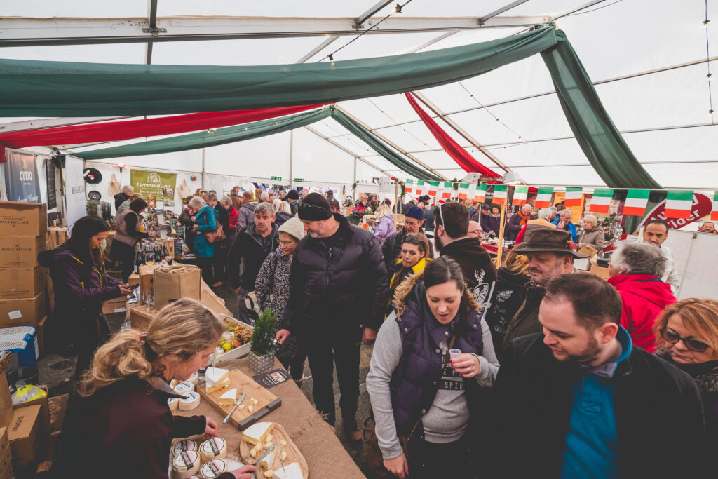 A busy marquee full of happy shoppers at Fowey Christmas Market